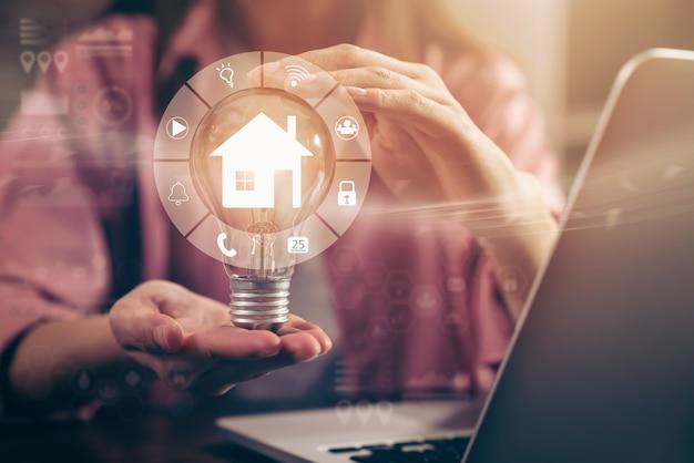 Hand, die glühbirne mit smart home-bedienfeld hält, symbole für erneuerbare energien mit nachhaltiger entwicklung.