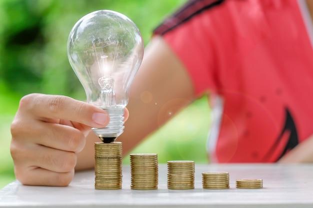 Hand, die glühlampe mit münzen hält, stapeln auf holztisch