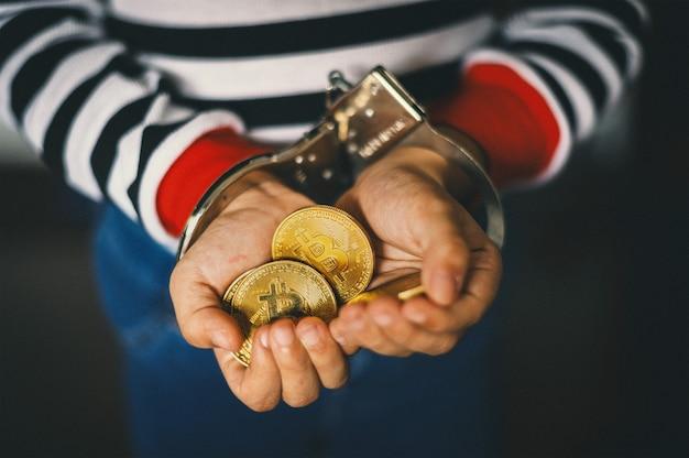 Hand, die goldenes bitcoin hält. krimineller mit handschellen, nachdem er ein verbrechen begangen hat
