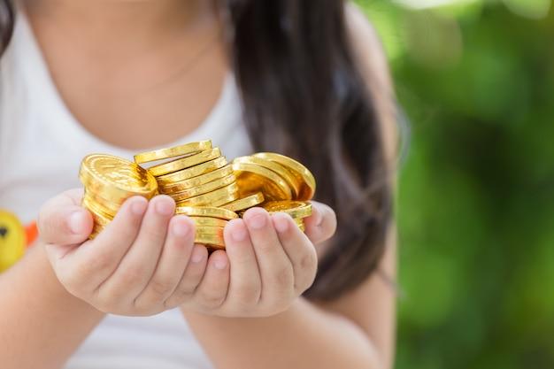 Hand, die goldenes münzenkonzept auf grünem hintergrund hält