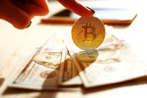 Hand, die goldenes virtuelles bitcoin-geld hält.
