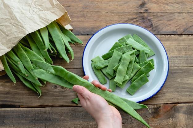 Hand, die grüne bohnen für das kochen des hölzernen hintergrundes vorbereitet. platz kopieren. ansicht von oben