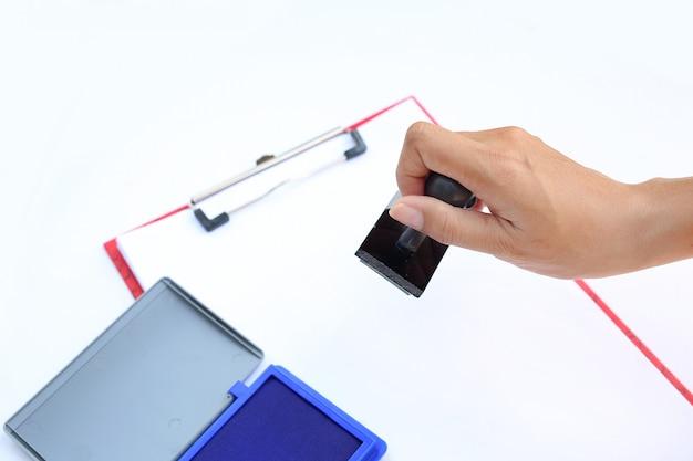 Hand, die gummistampfer mit blauer tintenauflage (kasten) auf weißbuch hält.