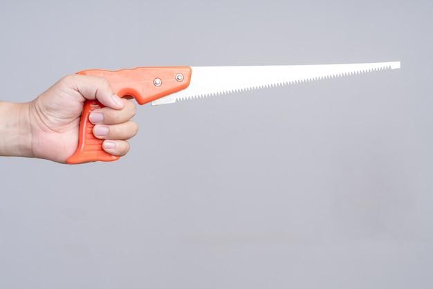 Hand, die handsäge mit plastikgriff hält