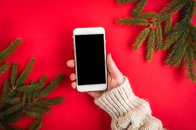 Hand, die handy auf rot mit weihnachtstannenzweigen hält.