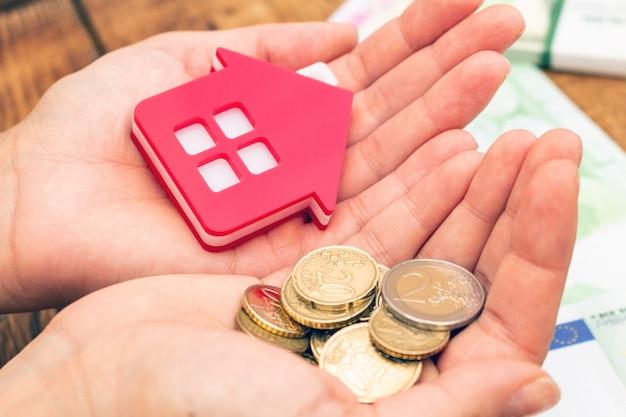 Hand, die haus nach hause und geld hält. immobilienkonzept