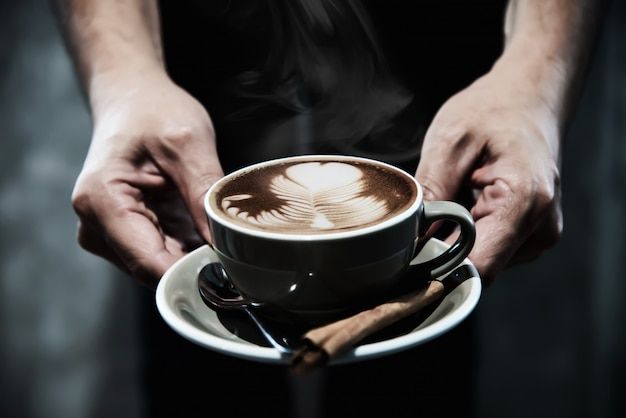 Hand, die heiße kaffeetasse hält