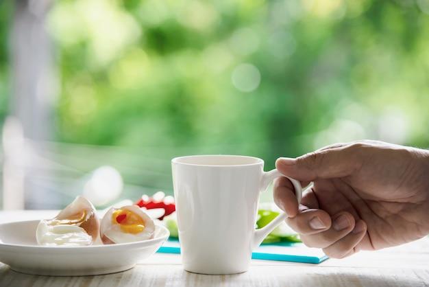 Hand, die heiße kaffeetasse mit gekochten eiern mit frischem gurkenkartoffel-zwiebelsalatfrühstückssatz mit grünem wald - frühstücksnahrungskonzept mit kapuze bedeckt