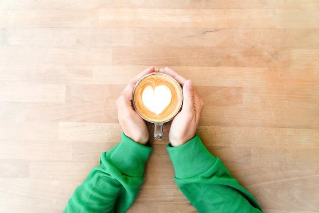 Hand, die heißen kaffee mit herzmilchschaum hält