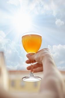 Hand, die helles cocktail vor dem himmel hält