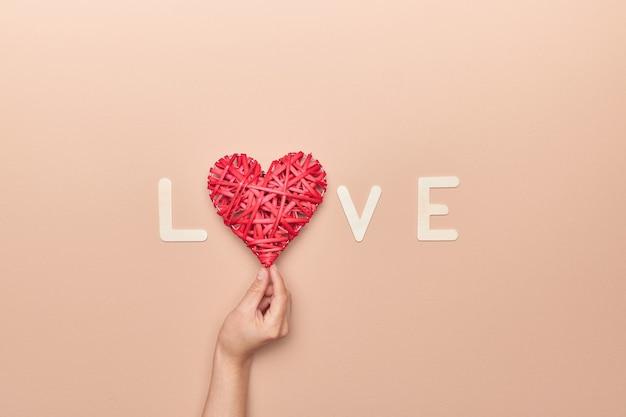 Hand, die herzdekoration in liebesphrase für valentinstag hält