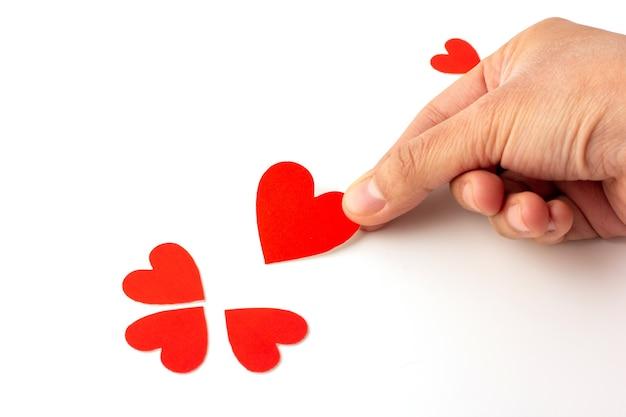 Hand, die herzförmiges rotes papier lokalisiert, konzeptliebe und valentinstag hält.