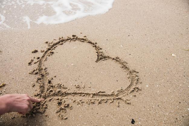 Hand, die herzform auf sand zeichnet