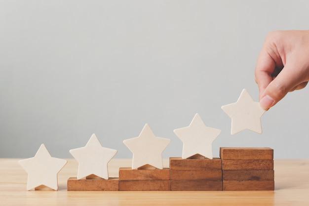 Hand, die hölzerne form mit fünf sternen auf tabelle setzt. das beste konzept für die bewertung des kundenerlebnisses durch exzellente unternehmensdienstleistungen