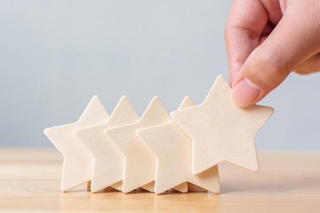 Hand, die hölzerne fünf-sterne-form auf tisch setzt. das beste exzellente business services rating für das kundenerlebniskonzept
