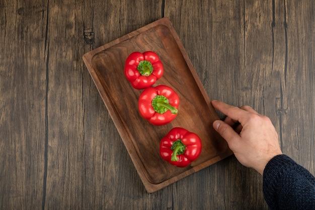 Hand, die hölzerne platte von frischen roten paprikaschoten auf holzoberfläche hält