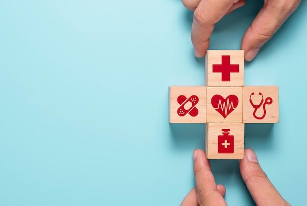 Hand, die hölzerne würfel der gesundheitsmedizin und der krankenhausikone auf blauen tisch setzt. krankenversicherungsgeschäft und investition.