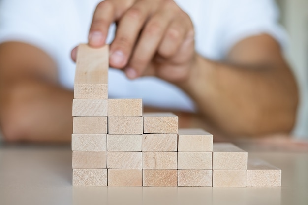 Hand, die holzblockstapelung als stufentreppe anordnet. leiter-karriere-pfad-konzept für den erfolgsprozess des geschäftswachstums, platz kopieren