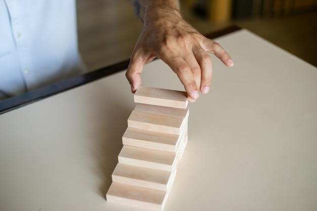 Hand, die holzblockstapelung als stufentreppe anordnet.