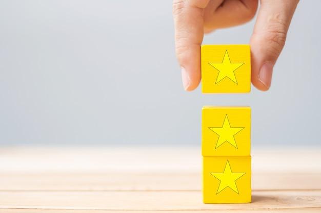 Hand, die holzklötze mit dem sternsymbol hält. kundenrezensionen, feedback, bewertung, ranking und servicekonzept.