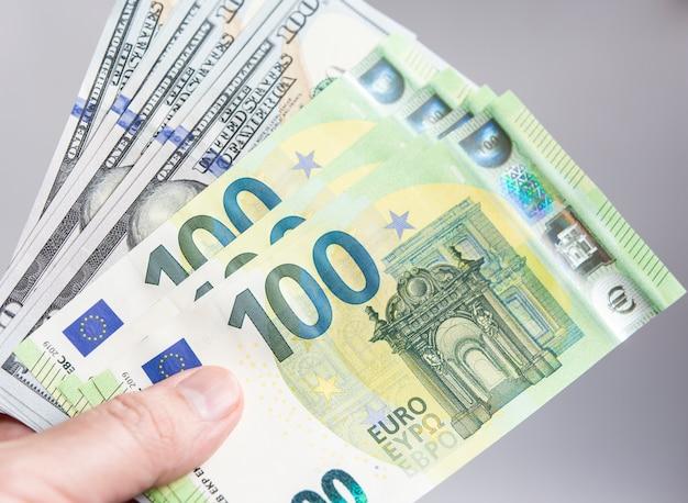 Hand, die hundert dollar- und eurorechnungen anhält