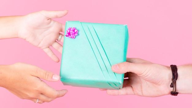 Hand, die ihrem freund eingewickelte geschenkbox über rosa hintergrund gibt