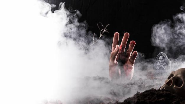 Hand, die im dichten nebel aus dem boden heraus haftet