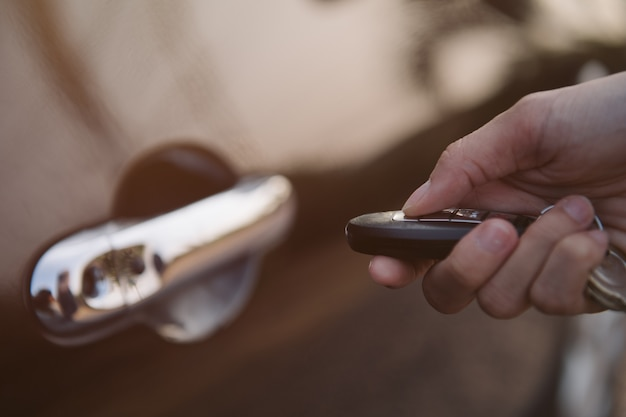 Hand, die intelligenten schlüssel hält, um türen des autos zu verriegeln