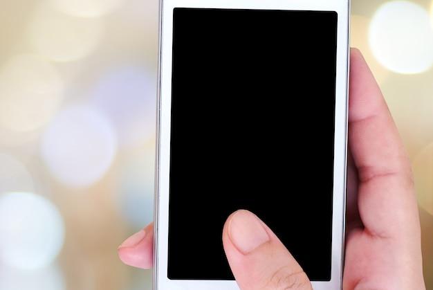 Hand, die intelligentes telefon über unschärfe bokeh hintergrund hält