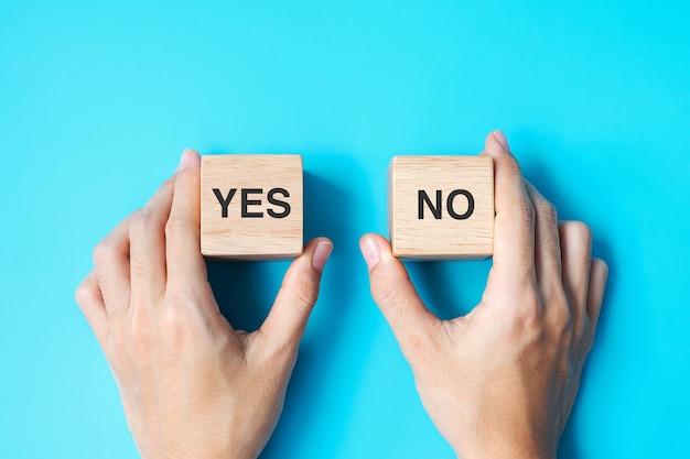 Hand, die ja- oder nein-block wählt. antwort-, frage- und entscheidungskonzept