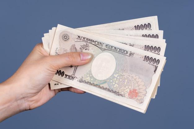 Hand, die japanische banknote hält