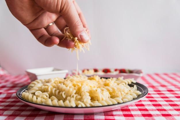 Hand, die käse auf frischen teigwaren besprüht