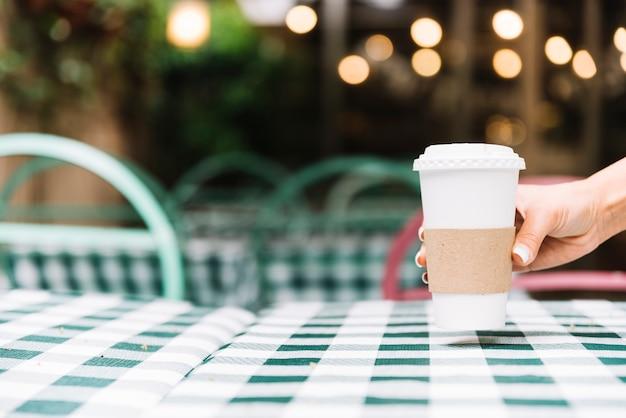 Hand, die kaffee auf eine tabelle setzt