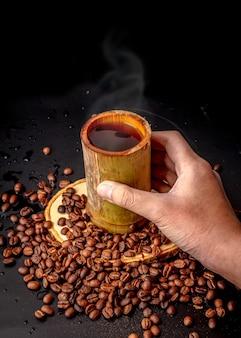 Hand, die kaffeebecher aus bambus hält, viele geröstete kaffeebohnen auf schwarzem hintergrund verstreut, dunkler kaffee hat rauch und aroma, getränk für die pause, morgen- und kaffeezeit, lokaler stil.