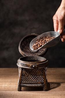Hand, die kaffeebohnen in weinlesebehälter gießt