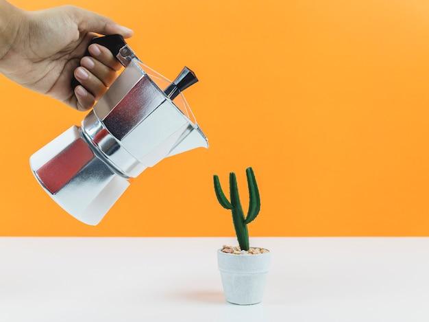 Hand, die kaffeespresso-hersteller mit einem kleinen grünen kaktus hält