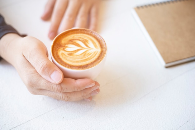 Hand, die kaffeetasse auf tabelle hält
