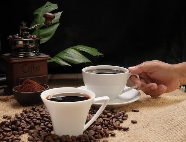 Hand, die kaffeetasse mit mühle, gerösteten bohnen, kaffeemehl über sackleinenhessisch auf schmutzholz-tischhintergrund hält