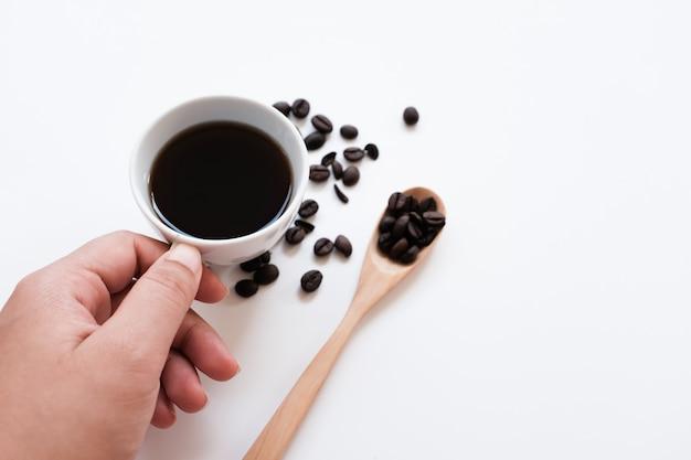 Hand, die kaffeetasse und bohnen auf einem weißen hintergrund hält