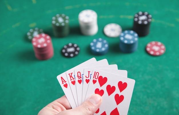 Hand, die karten mit kasino-chips auf dem grünen tisch hält.