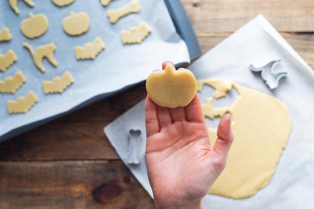 Hand, die kekse in verschiedenen formen für halloween zubereitet. platz kopieren.