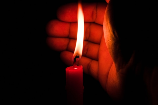 Hand, die kerzenlicht vor dem wind in der dunkelheit auf schwarzem hintergrund schützt