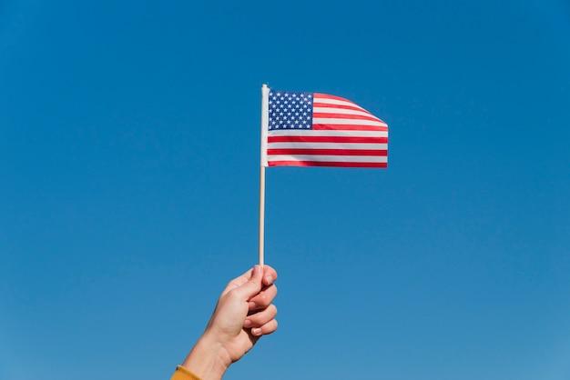 Hand, die kleine amerikanische flagge hält