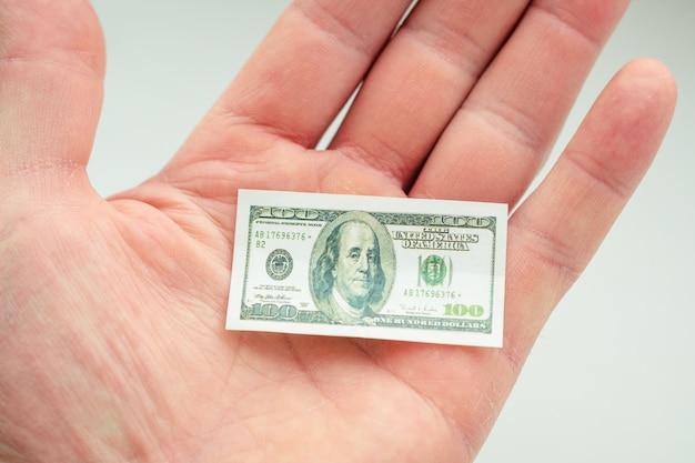 Hand, die kleine banknote des us-dollars hält