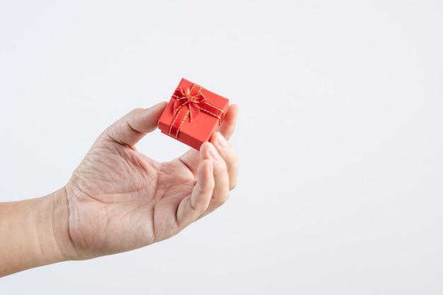 Hand, die kleine rote geschenkbox mit band und bogen für special hält