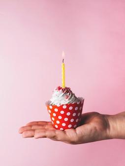 Hand, die kleinen kuchen mit kerze hält