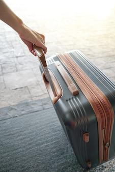 Hand, die koffer in einem flughafen hält. frau mit handgepäck im flughafen.