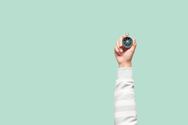 Hand, die kompass auf grünem hintergrund hält