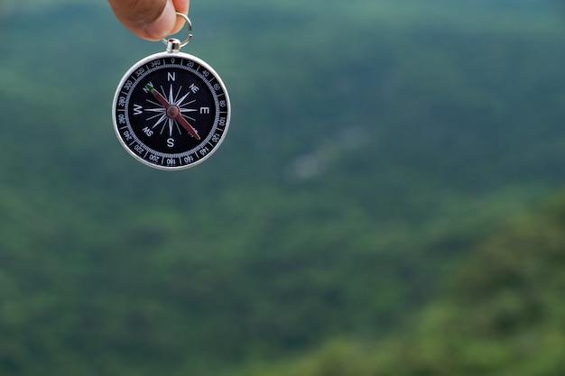 Hand, die kompass gegen grünen baum montain hintergrund hält.