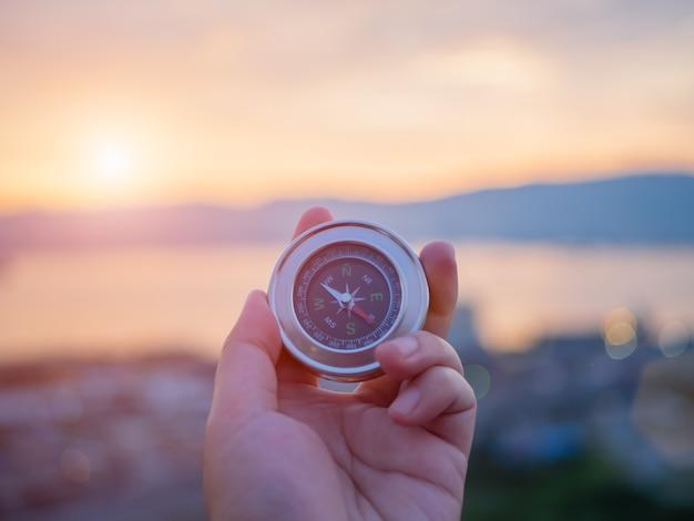 Hand, die kompass mit gebirgs- und sonnenunterganghimmelhintergrund hält.